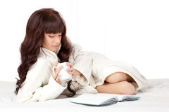 Woman reading book laying on bed. Beautiful woman reading book laying on bed and holding mug Stock Photo