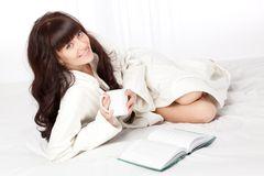 Woman reading book laying on bed. Beautiful woman reading book laying on bed and holding mug Stock Images
