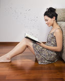 Woman reading book with letters flying forward Royalty Free Stock Photo