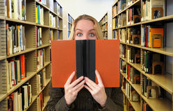 Woman Reading Book in Library. A woman is holding a book in a library. Use it for an education or research concept Stock Photo
