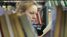 Woman is reading a book in library. She is in the corridor between the books. Young woman is reading a book in the library. Many books, she is in the corridor stock video footage