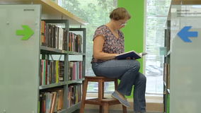 Woman reading book in library stock video