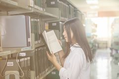 Woman reading book in library Stock Photos