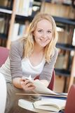 Woman reading book in library Stock Images
