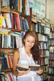 Woman reading a book in library Stock Photos