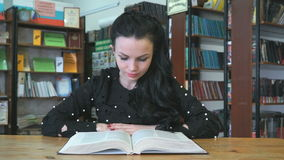 Woman reading book at library to find information. Young woman reading book at library to find information stock video