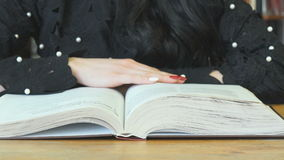 Woman reading book at library to find information stock footage