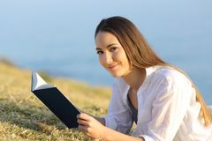 Woman reading a book looking at camera on the grass Stock Photography