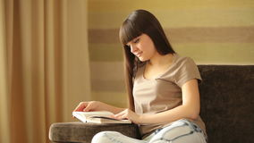 Woman reading book and looking at camera with stock video