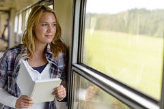 Woman reading book looking out train window Stock Photos