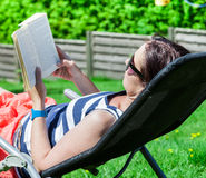 Woman while reading a book Stock Photos