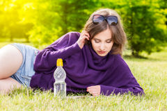 Woman reading book lying down on grass in park Stock Image