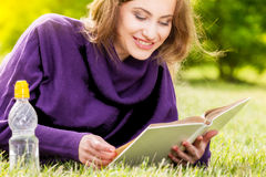 Woman reading book lying down on grass in park Stock Photos