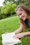 Woman reading a book while lying in a park Royalty Free Stock Photo