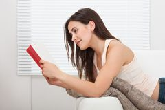 Woman reading book while lying on sofa Stock Photo