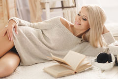 Woman reading a book lying on the sofa. Stock Image