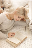 Woman reading a book lying on the sofa. Royalty Free Stock Photo