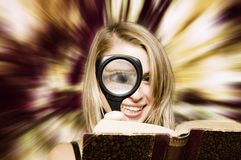 Woman reading book with a magnifier Stock Photography
