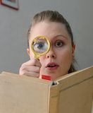 Woman reading a book with magnifying glass Royalty Free Stock Image
