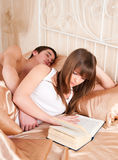Woman reading a book and man sleeping. Woman reading a book and  man sleeping next to her Stock Image