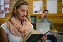 Woman reading book while man talking on phone in background stock images