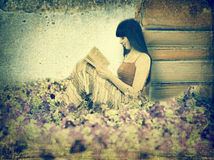 Woman reading book on the meadow Stock Image