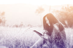 Woman reading book in meadow Stock Photo
