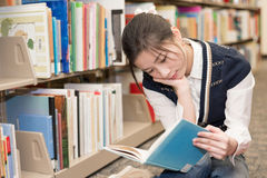Woman reading a book near bookshelf Stock Photo