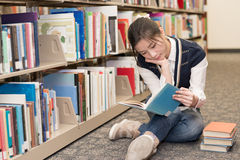 Woman reading a book near bookshelf Stock Photos