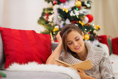 Woman reading book near Christmas tree Royalty Free Stock Photo