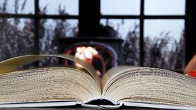 Woman reading book next to the fireplace and window, hand turn page of a book, hardcover book open in the middle