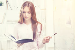 Woman reading a book in office Royalty Free Stock Image