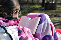 Woman reading a book outdoor. Young woman sitting outdoors, covered with blanket and reading a book Royalty Free Stock Photos