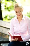 Woman reading book outdoors Royalty Free Stock Photos