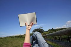 Woman reading book outdoors. Woman reading book in outdoor park Royalty Free Stock Photography