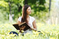 Woman reading book outdoors Royalty Free Stock Photo