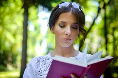 Woman Reading Book Outdoors in Peaceful Forest Stock Images