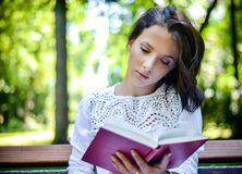 Woman Reading Book Outdoors in Peaceful Forest Stock Photo
