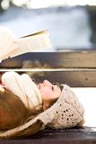 Woman reading book outdoors at winter time Royalty Free Stock Photography