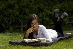 Woman reading book on grass in park Stock Photo