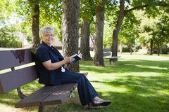 Woman reading book in a park Royalty Free Stock Image