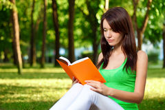 Woman reading book at park Royalty Free Stock Image