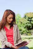 Woman reading a book in the park Royalty Free Stock Image