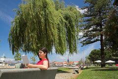 Woman reading book in park Stock Photos