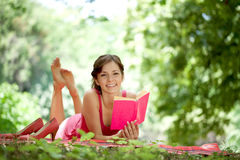 Woman reading book in park Stock Photography