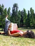 Woman reading book in park Stock Image