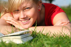 Woman reading book in the park. Woman lying down in the park Royalty Free Stock Image