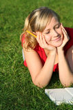 Woman reading book in the park. Woman lying down in the park Royalty Free Stock Photos