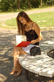 Woman reading book in park Royalty Free Stock Image
