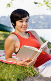 Woman reading book in park Stock Photo